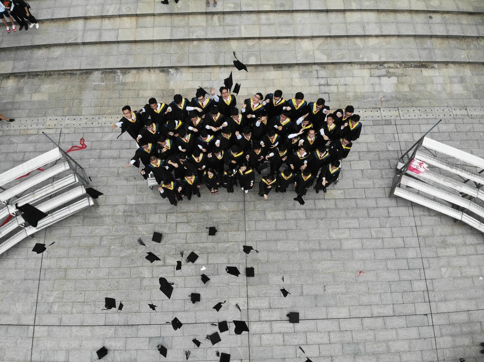 group of graduates throwing academic hats