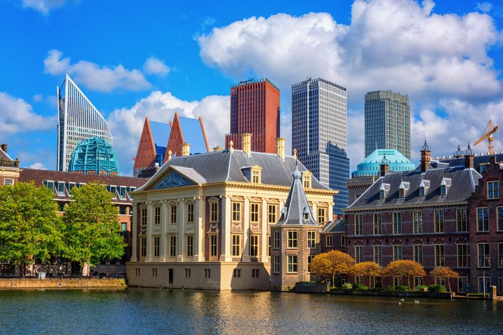 Binnenhof castle (Dutch Parliament) background with the Hofvijver lake against a background of skyscrapers and blue cloudy sky, Hague (Den Haag), Netherlands